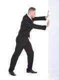 Businessman pushing the edge of a blank white sign Royalty Free Stock Photography