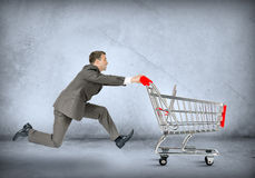 Businessman pushing empty shopping cart Stock Photo