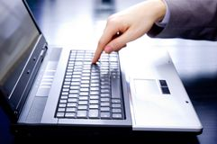 Businessman pushing the enter button. Businessman's out-of-focus hand is pushing the enter button of a notebook Royalty Free Stock Photo