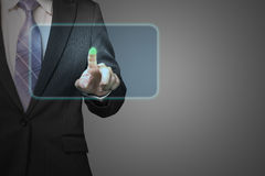 Businessman pushing on future touch screen icon in space with da. Rk background Royalty Free Stock Photos