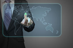 Businessman pushing on future touch screen icon with world wide. Map in space with dark background Stock Photo