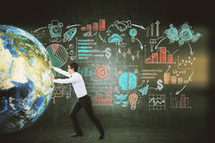 Businessman pushing globe near blackboard Stock Photography