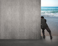 Businessman pushing gray concrete wall away Royalty Free Stock Photos