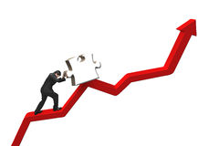 Businessman pushing heavy jigsaw puzzle upward on red trend line. Isolated on white background stock image