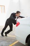 Businessman pushing his broken down car Royalty Free Stock Photos