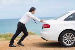 Businessman pushing his car Royalty Free Stock Images