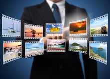 Businessman pushing many image in film button Stock Photos