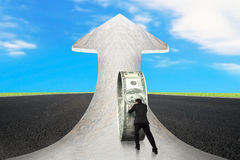 Businessman pushing money circle on arrow marble road with sky Royalty Free Stock Photos