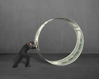 Businessman pushing money circle in concrete background Stock Photography