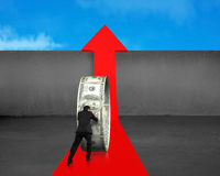 Businessman pushing money circle on growing red arrow. With concrete wall and blue sky background stock photos