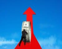 Businessman pushing money circle on growing red arrow with sky. Rear view businessman pushing money circle on growing red arrow in blue sky background royalty free stock image