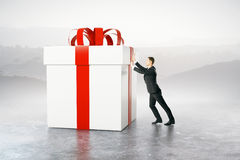 Businessman pushing present box. Businessman pushing huge present box on abstract background. 3D Rendering stock illustration