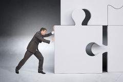 Businessman Pushing Puzzle Piece Stock Photography