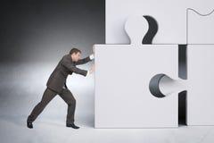Businessman pushing puzzle piece Stock Photography