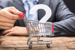 Businessman Pushing Question Mark In Shopping Cart. Midsection of businessman pushing question mark in shopping cart on wooden table stock photography