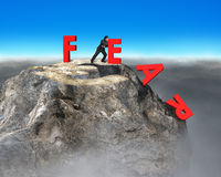 Businessman pushing red fear word down with euro sign. On top of rocky mountain, overcoming fear concept Stock Photo