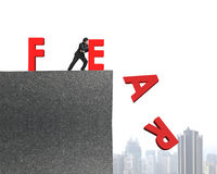 Businessman pushing red fear word down. On top of concrete building, overcoming fear concept Stock Images