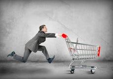 Businessman pushing shopping cart Royalty Free Stock Photography