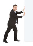 Businessman Pushing Something Over White Background. Full length side view of young businessman pushing something over white background Royalty Free Stock Image