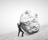 Businessman pushing stone. Up on hill Stock Images