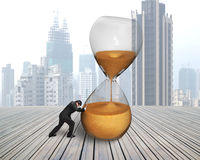 Businessman pushing tilt hourglass Stock Photos