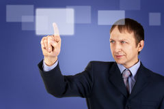 Businessman pushing on a touch screen Stock Images