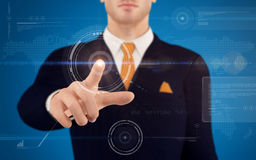 Businessman pushing on a touch screen button. Young businessman pushing on a touch screen button in futuristic virtual interface. See more business illustration Stock Images