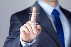 Businessman pushing on a touch screen interface Stock Photos