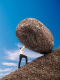 Businessman pushing up boulder. Businessman rolling up giant boulder on slope over blue sky Stock Photos