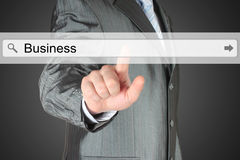 Businessman pushing virtual search bar with business word Stock Photography