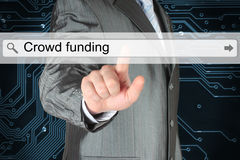 Businessman pushing virtual search bar with crowd funding words Stock Photos