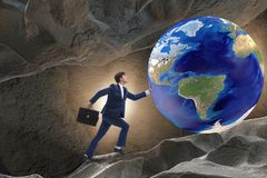The businessman pushing the world in challenge concept. Businessman pushing the world in challenge concept Stock Image