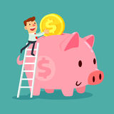 Businessman put gold coin in his piggy bank. Happy businessman climb up a ladder to put gold coin in his large piggy bank. Saving concept Stock Photos