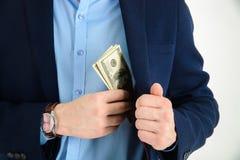 Businessman put money in his suit pocket - closeup