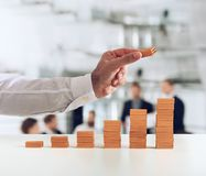 Businessman puts a brick on a bricks pile. Concept of growing statistics and success. Businessman puts a brick on a static made bricks. Concept of growing stock photos