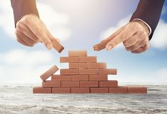 Businessman puts a brick to build a wall. Concept of new business, partnership, integration and startup royalty free stock images