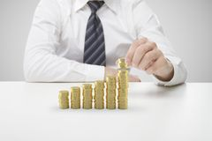 Businessman puts coins. Businessman hand puts  gold coins on table Stock Image
