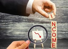 Businessman puts a cube with the word income and down arrow. The concept of reducing profits and incomes. lower salary, wage rates. Demotion, career decline royalty free stock image