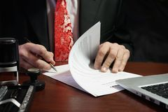 A businessman puts his signature on the contract stock images