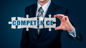 The businessman puts on the virtual puzzles word competence. The business concept. The businessman puts on the virtual puzzles word competence. The business stock photo