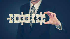 The businessman puts on the virtual puzzles word success. The business concept. Stock Images