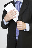 Businessman puts a white envelope in his pocket Stock Images