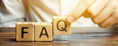 Free Businessman Puts Wooden Blocks With The Word FAQ Frequently Asked Questions. Collection Of Frequently Asked Questions On Any Stock Photo - 159622540