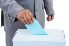 Businessman putting ballot in vote box Stock Image