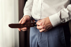 Businessman putting on a belt. Man puts on brown belt. Focus on. The buckle. Groom holding hands on the belt, wedding suit Stock Photos
