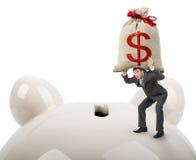 Businessman putting big money bag in piggy bank Royalty Free Stock Photo