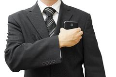 Businessman putting big smart phone into pocket Stock Images