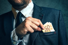 Businessman putting cash money in his pocket Stock Photo