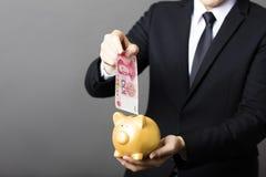 Businessman  putting cash yuan into  piggy bank. Business man  putting cash yuan into  piggy bank Stock Photo