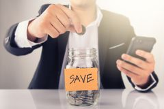 Businessman Putting Coin Into Jar Labelled Savings. Businessman Putting Coin Into Jar,save money concept Stock Images